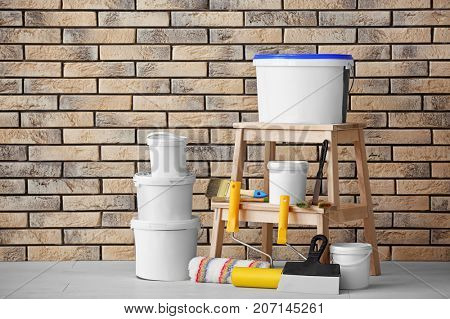 Composition with paint and decorator's tools near brick wall