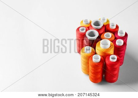 Red and orange threads of different shades on white background