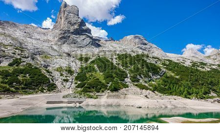 Extreme tourism at the Dolomites. Glacial lake with clear green cold water, marmolada. Lago di Fedaia, Dolomites