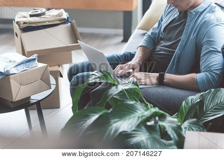 Smiling young man typing on keyboard of notebook computer while locating on cozy couch in apartment at home. Post box with clothing on background