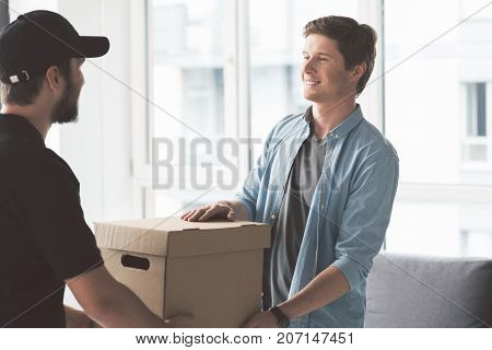 Portrait of outgoing customer taking new carton box with delivery from worker. Delivery concept