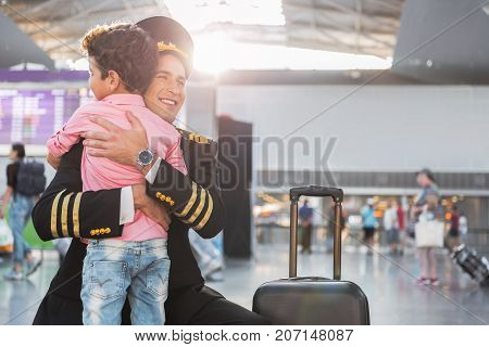 I am so happy to see you. Pilot is squatting and hugging his son. He looking aside with smile. Copy space on right side