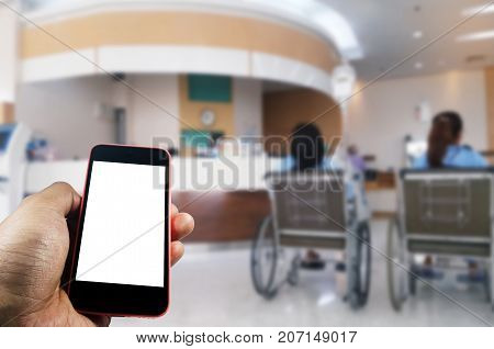 hand using smart phone with blurred image of patients in a wheelchair waiting in lobby at hospital background medical internet network connection searching social media payment online concept