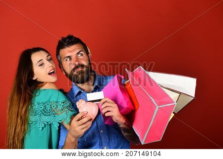 Couple In Love Holds Shopping Bags On Red Background.