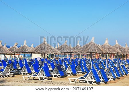 Comfortable sun loungers on sea beach at resort