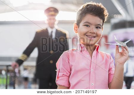 Cheerful little child is holding toy airplane and looking at camera with smile. Father pilot standing on background. Waist-up portrait. Copy space on left side