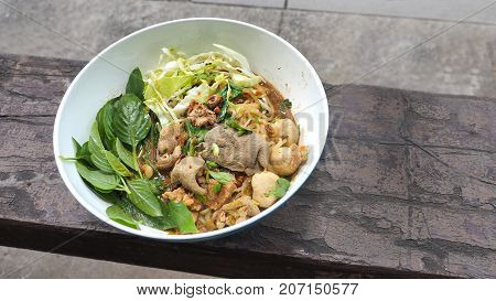 Boat noodles pork in plastic white bowl Thai food classic and popular menu and ready to eat on vintage wood has copy space