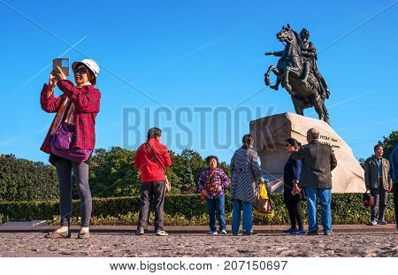 St. Petersburg, Russia - September 24, 2017: Tour group from China near the monument to the bronze Horseman. A woman makes a selfie with a monument.
