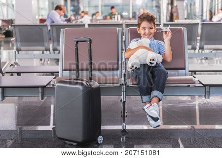 Merry male child is sitting on chair near suitcase in waiting hall and looking at camera with wide smile. He holding teddy bear. Portrait. Copy space on left side