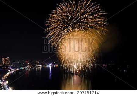 Fireworks over the sea beach with dark black sky background and city view