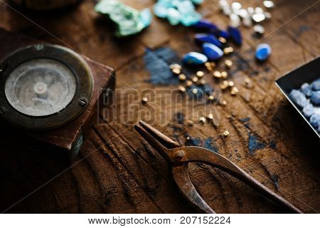 Exploring mining, and inspecting gems. Treasure hunting. Gold and gems on rough wooden surface.