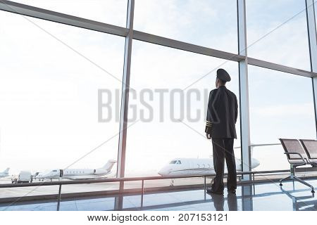 Pilot is standing near glass wall and glancing thought it on aircrafts. He locating in waiting hall of airport. Low angle. Copy space on left side
