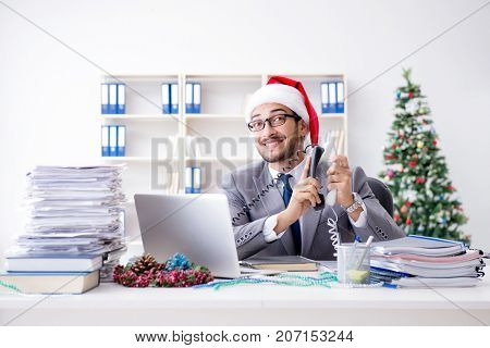 Young businessman celebrating christmas in the office