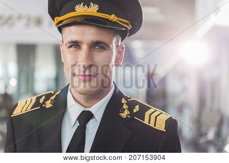 Cheerful pilot wearing uniform is looking at camera with light smile. Portrait. Copy space on right side