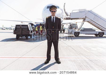 Confident pilot wearing uniform and sunglasses is standing afore big air-vehicle. Full length portrait. Copy space
