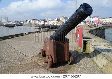 Ancient Ships Canon Situated On A Dockside With A Harbour In The Background