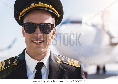 Glad pilot wearing sunglasses is locating afore plane and looking at camera with bright smile. Portrait. Copy space