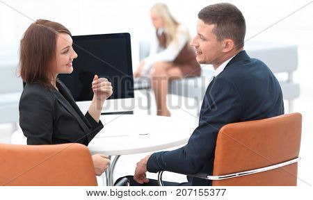 business associates talking at a Desk.