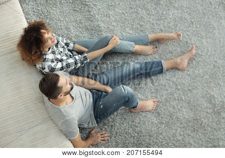 newlywed couple sitting on a carpet in a new living room
