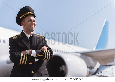 Glad pilot wearing uniform is looking ahead with affable smile. He standing afore tremendous aircraft. Waist up portrait. Copy space