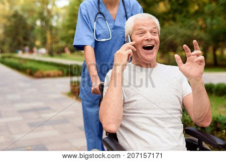 Happy Old Man Sitting In A Wheelchair And Talking To Someone On The Phone