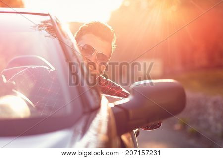Fashion man sitting in luxury cabriolet car outdoors.