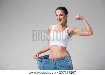 I did it. Portrait of joyful fit girl showing her slim figure in oversized pants after workout. She is straining her muscles on arm with proud and winking. Isolated and copy space