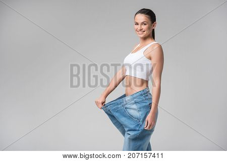 Portrait of outgoing girl showing thin figure after fitness training. She is wearing oversized pants and laughing. Lady is standing and looking at camera with satisfaction. Isolated and copy space