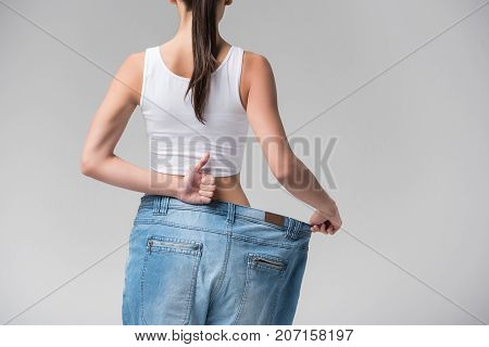 I am satisfied with my figure. Slim girl is wearing oversized pants after dieting. She is turning back to camera and giving thumb up. Isolated and copy space
