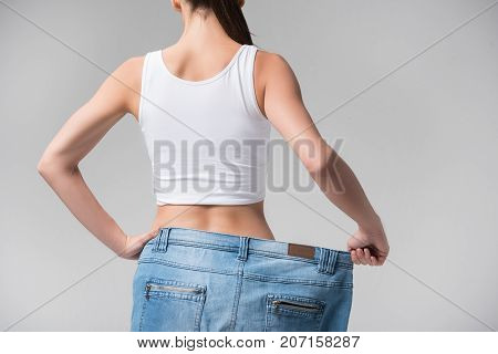 Close up of female back. Young woman is presenting her slim figure after exercising. She is stretching oversized pants sideways and standing with arm akimbo. Isolated