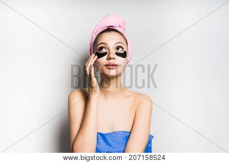 girl with a towel on her head puts a mask on her face