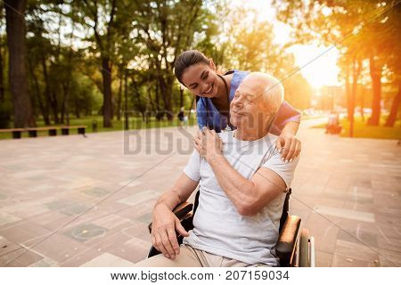 The Old Man Who Sits In A Wheelchair Holds The Nurse By The Hand, Who Laid Her Hand On His Shoulder