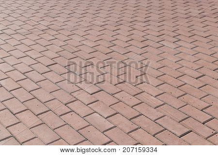 The square or on a sidewalk lined with brown tiles paving stones. Pavers laid out in several rows with offset. The paving surface is rough with small hollows.