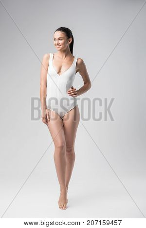 Beauty concept. Full length portrait of happy fit young woman posing in white swimsuit. She is standing with arm akimbo and smiling. Isolated