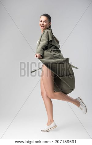 Beautiful and free. Full length portrait of joyful young woman having fun while wearing coat. She is smiling. Isolated
