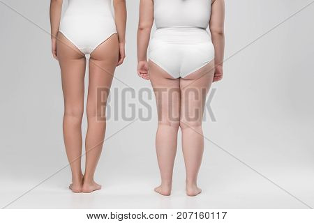 Difference is visible. Close up of ass and legs of two young thin and thick women. Focus on cellulite and smooth skin. Isolated