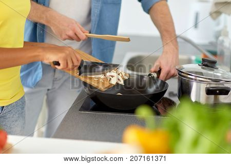 food, cooking, people, international and healthy eating concept - multiethnic couple with pan frying champignons at home kitchen