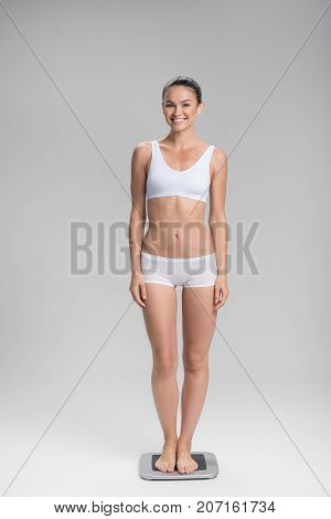 Full length portrait of happy young slim woman standing on scales. She is looking at camera and smiling. Isolated