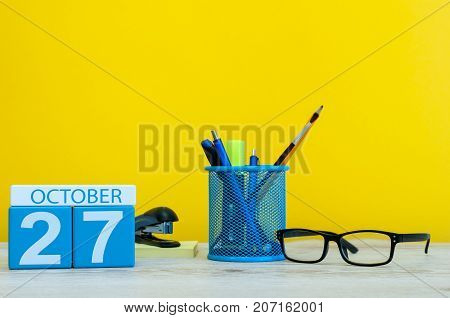 October 27th. Day 27 of october month, wooden color calendar on teacher or student table, yellow background . Autumn time.