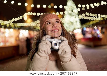 holidays, photography and people concept - beautiful happy young woman with camera at christmas market in winter evening