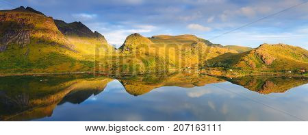 Perfect reflection of colorful mountains in calm water. Norway fjord in the sunlight. Warm sunny day on Lofoten islands.