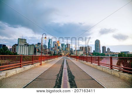 Downtown Minneapolis Minnesota at night time as seen from the famous stone arch bridge