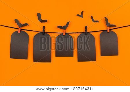 Halloween flock bats and black blank labels tomb hanging on clothespins on orange background mock up. Template for advertising design cover.