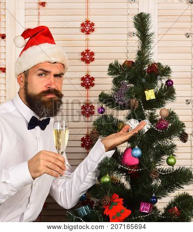 Man With Beard Holds Champagne Glass And Shows Fir Tree