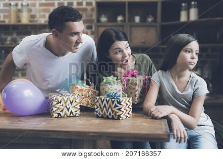 A Man And A Woman Cheerfully Encourage The Girl And Offer Her Gifts. The Girl Looks Indifferently Aw