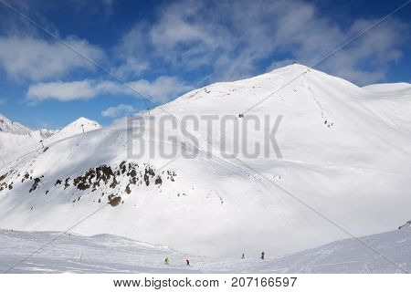 Skiers And Snowboarders Downhill On Trace And Mountains With Clouds