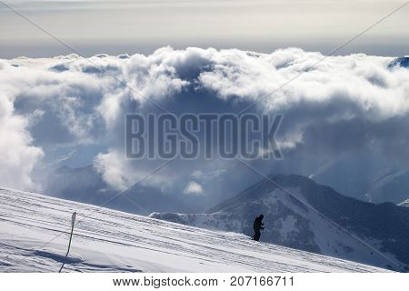 Skier Downhill On Ski Slope And Sunlight Storm Clouds