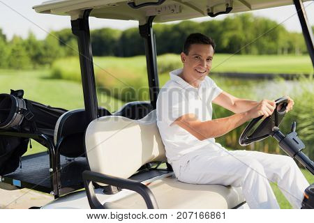 Time For A Game Of Golf. A Man In A White Suit Is Riding A White Golf Cart