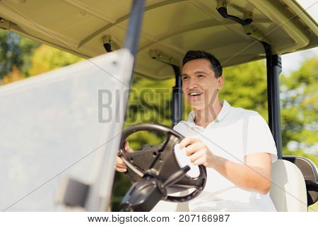 Smiling Man In A White Golf Cart Enthusiastically Rides Forward