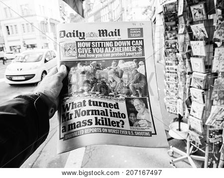 PARIS FRANCE - OCT 3 2017: Man buying Daily Mail newspaper with socking title and photo at press kiosk about the 2017 Las Vegas Strip shooting in United States with about 60 fatalities and 527 injuries